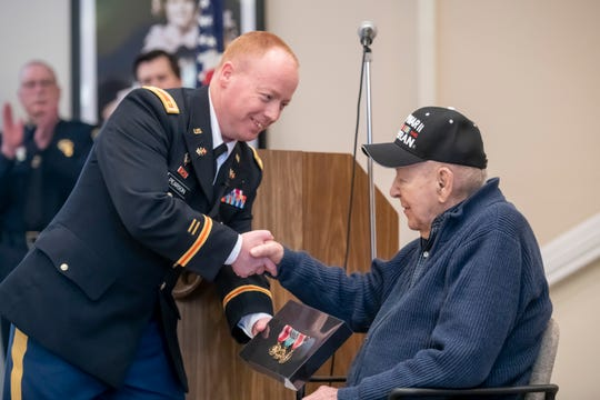 Major Daniel Pearson, Commander of the U.S. Army recruiting company in Dearborn, left, presents Army veteran Henry Kroll with three medals from his time in World War II.