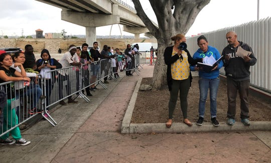 FILE - In this Sept. 26, 2019 file photo volunteers in Tijuana, Mexico, call names from from a waiting list of people to claim asylum at a border crossing in San Diego.
