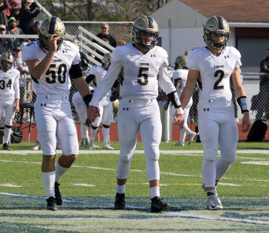 Corning captains Seth Hogue (50), Blake VanWoert (5) and Joey Ott (2) walk onto the field for the coin toss before an 8-0 win over Elmira on Oct. 26, 2019 at Ernie Davis Academy.