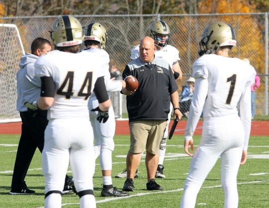 Corning head coach George Bacalles, center, talks to his players during warm-ups before an 8-0 win over Elmira on Oct. 26, 2019 at Ernie Davis Academy.
