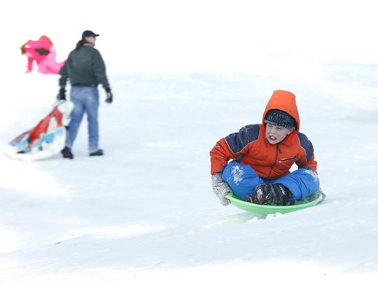 Kids take advantage of the recent snowfall to sled down Buttermilk Creek Park's sledding hill in 2015.