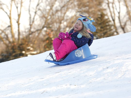 A young girl closes her eyes as she flies down the sledding hill at Buttermilk Creek Park in 2015.