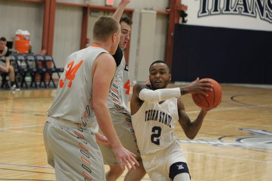 Terra State Community College's Kiran Taylor drives on two Heidelberg University  JV defenders Wednesday at the Titans' men's basketball home opener. The Titans pulled away in the second half and won 87-61.