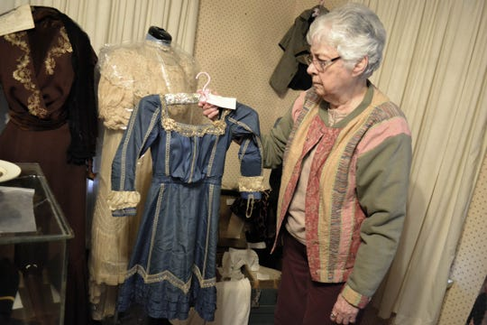 Green Springs is home to the world's largest natural sulfur spring, and, here, Carolyn Young holds a dress which once belonged to Lotia Perin, who drowned in the spring at the age of 14 in 1904. Her family donated the dress to keep her memory alive.