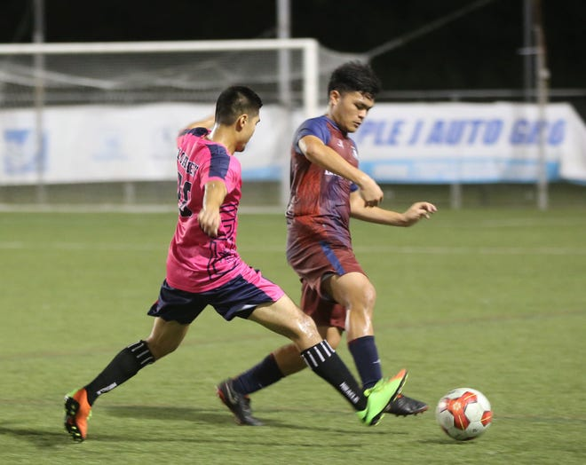 Bank of Guam Strykers' Noah Bamba works to direct the ball away from Lots of Art Tattoo Heat's Jan Flores in a Week 4 match of the Budweiser Soccer League Premier Division at the Guam Football Association National Training Center.