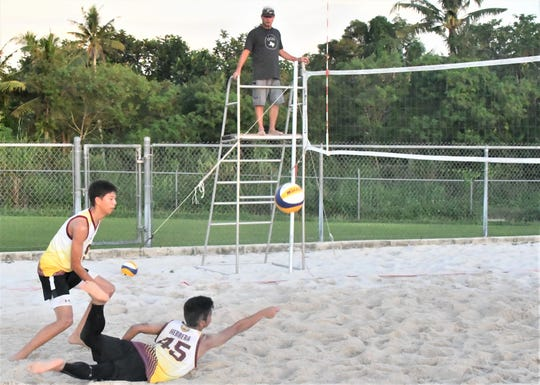 FD's No. 45 Jacob Herrera dives for a dig while teammate Jeremiah Nguyen waits to play it off the net in their match against Tiyan's Calib Naputi/VJ Rosario. FD won the overall contest 2-1, creating a 3-way tie for first place in IIAAG Boys Beach Volleyball Nov. 14 at the GFA National Training Center's sand courts.