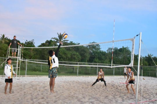 In this file photo from Nov. 14, Tiyan High School's VJ Rosario swings away against FD's Jacob Herrera, left and Jeremiah Nguyen against FD. Rosario and his partner, Calib Naputi, defeated FD's Kaleb Tennessen and Raymond Castro in a three-set thriller to give their team a win, a 7-1 record and the first-ever IIAAG Boys Beach Volleyball regular season title.