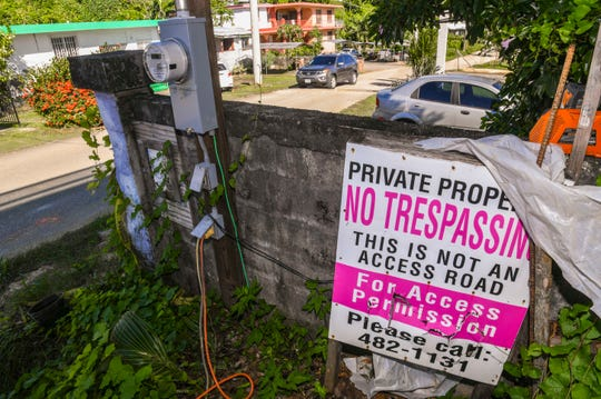 A motorist travels on Vicente Salomon Drive in Agana Heights as a private property sign can be found along the roadway on Thursday, Nov. 14, 2019.