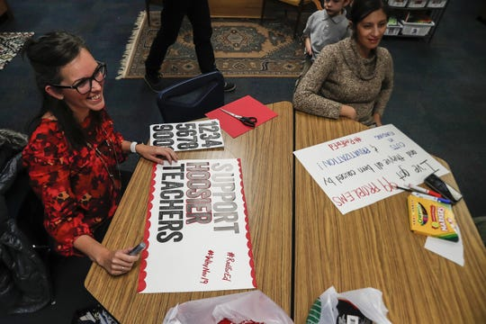 Educator Beth Whitaker and Indianapolis Public Schools teacher Emily Salinas sit at a table making sings for Red for Ed rally, Thursday, Nov. 14, 2019, at Center for Inquiry 2, Indianapolis.