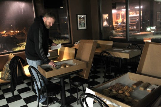 Scott Ward checks orders at Daylight Donuts before sending out deliveries early Saturday, Jan. 11, 2014.