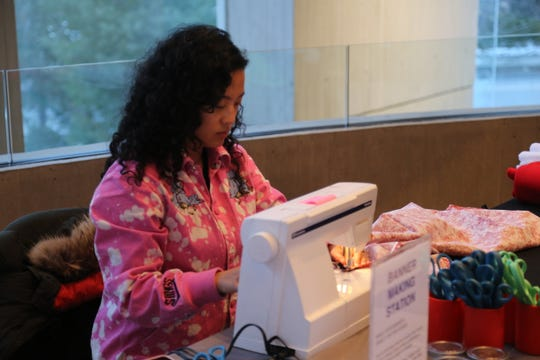 Aram Han Sifuentes uses a sewing machine at a protest banner workshop at Cornell University's Johnson Museum of Art.