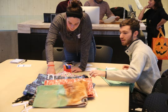 Rayna Klugherz, a 20-year-old Cornell junior majoring in history, and Brandon Hoak, a 21-year-old junior majoring in design and environmental science, look through different fabrics at a protest banner workshop.