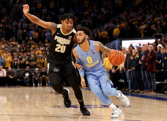Nov 13, 2019; Milwaukee, WI, USA; Marquette Golden Eagles guard Markus Howard (0) drives for the basket around Purdue Boilermakers guard Nojel Eastern (20) during the first half at Fiserv Forum. Mandatory Credit: Jeff Hanisch-USA TODAY Sports