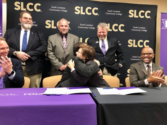 South Louisiana Community College Chancellor Natalie Harder and Northwestern State University President Chris Maggio hug after signing an agreement Thursday creating a pathway from SLCC's associate degree program in civil survey and mapping to NSU's bachelor degree program in resource management with a concentration in GEO computation at NSU.
