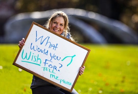 """Courier Journal reporter Maggie Menderski held up a sign asking, """"What would you wish for?"""" in front of the wishbone sculpture at The Speed Art Museum."""