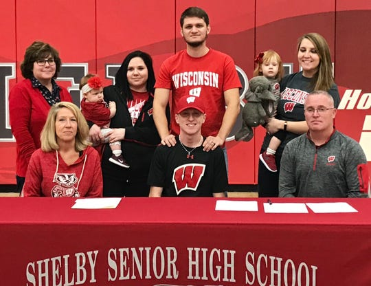 Shelby's Caleb Brown is flanked by his mom, Christa, and dad, Jay, and joined by other family members after signing a national letter of intent Wednesday to attend the University of Wisconsin.