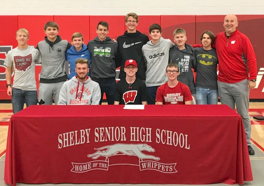Shelby cross country/track state champion Caleb Brown is surrounded by the Whippets' cross country team and coach Chris Zuercher after signing his national letter of intent to attend the University of Wisconsin on Wednesday in the high school gymnasium.