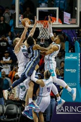 Memphis Grizzlies guard Ja Morant, second from left, drives past Charlotte Hornets' Cody Zeller, left, Cody Martin and Charlotte Hornets forward Miles Bridges, right, to hit the game-winning shot in the second half of an NBA basketball game in Charlotte, N.C., Wednesday, Nov. 13, 2019. Memphis won 119-117. (AP Photo/Nell Redmond)