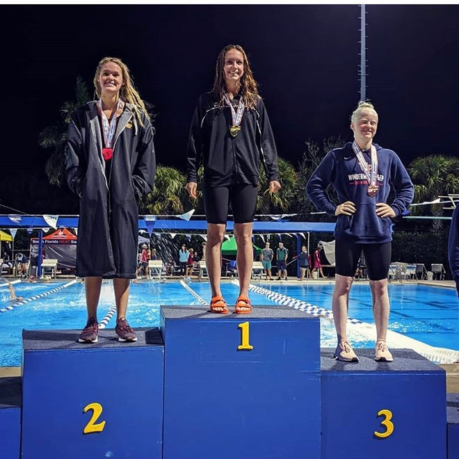 Marco Island resident and St. John Neumann senior Maddy Burt stands atop the podium after winning the Class 1A state championship in the 100-yard butterfly. Burt's gold was her sixth medal in four state appearances and the first-ever gold by a St. John Neumann swimmer.