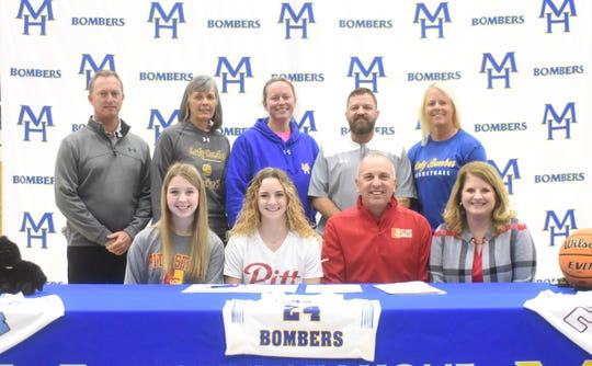 Mountain Home's Emma Martin (front, second from left) signed her National Letter of Intent on Thursday to play college basketball at Pittsburg State. Pictured with Martin are: (front row) her sister Abby Martin, her father Matt Martin, her mother Ann Martin; (back row) MHHS athletic director Mitch Huskey, former Junior Lady Bomber coach Brenda Yancey, Lady Bomber assistant Jill Daves, Lady Bomber head coach Dell Leonard, and Junior Lady Bomber coach Lindsey Leonard.