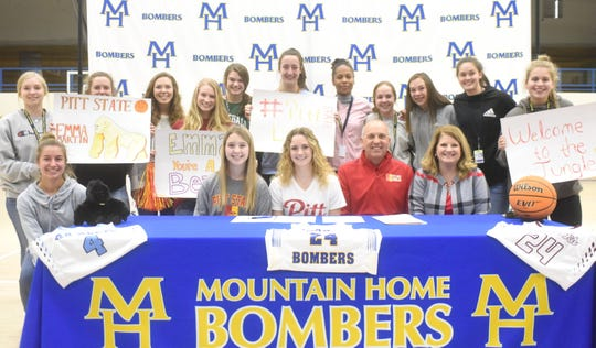 Mountain Home's Emma Martin is surrounded by Lady Bomber teammates as she signed with Pittsburg State on Thursday.