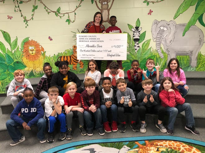 Marcellus Davis, a fourth-grader at Wetumpka Elementary School, with his teacher Kimberly Deem and classmates. Marcellus received a $100 check for a winning essay.