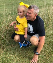Former Daleville cross country coach David Beard is pictured with his granddaughter during a meet. After 32 years as the Broncos' coach, Beard retired at the end of the 2019 season.