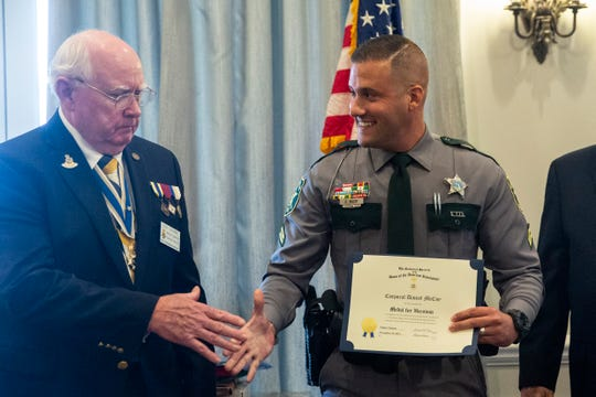 Corporal Daniel McCoy, center, shakes hands with President Leonard Crame for Naples Chapter NSSAR, left, after being presented with the Medal for Heroism during the annual public service awards presentation on Thursday, November 14, 2019, at the Tiburón Golf Club in North Naples.
