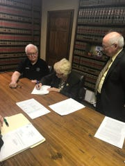 St. Landry Parish president Bill Fontenot and Opelousas attorney Patrick Morrow watch as Mavis Fontenot representing the St. Luc French immersion non-profit group signs a bill of sale allowing the purchase of a former community hospital in Arnaudville from St. Landry Parish government.