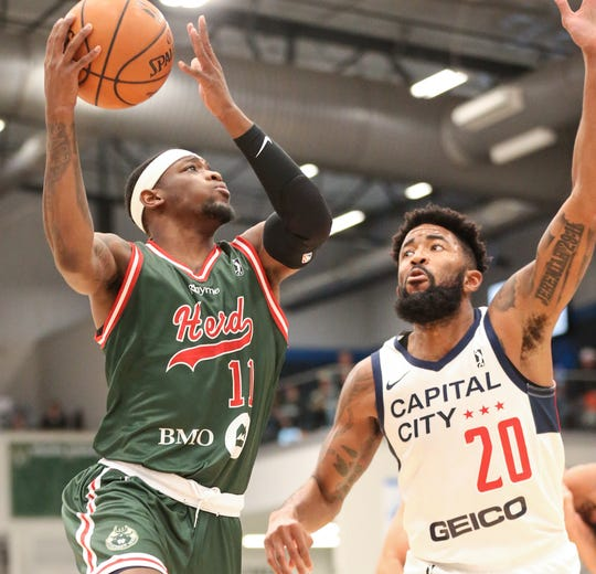 The Wisconsin Herd's Shannon Bogues (11) shoots over the Capital City Go-Go's Mike Cobbins (20) during their game Wednesday in Oshkosh.