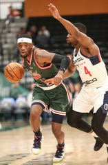 The Wisconsin Herd's Shannon Bogues (11) drives past the Capital City Go-Go's Ike Iroegbu (4) during their G League game Wednesday in Oshkosh.