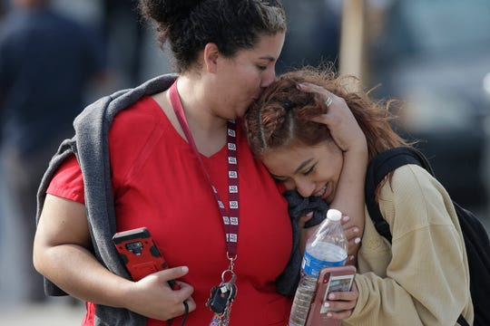 Parent Alicia Leon, left, kisses her daughter, Alejandra Cruz, a tenth grader, as they reunite after a lock down at the Esteban Torres High School in unincorporated East Los Angeles Wednesday, Nov. 13, 2019. A sheriff's deputy fatally shot a man wielding a sword, after he had climbed over the school fence. The man advanced toward a deputy and continued ignoring instructions to drop the weapon. One deputy opened fire; it was not clear how many times the deputy shot at the man. The man, whose identity has not been released, was pronounced dead at the scene. No deputies were injured.