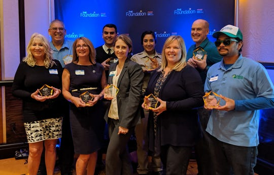 A group of honorees pose with their awards.