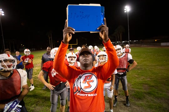 Palm Springs High School football offensive coordinator Malcom Munning Jr. runs a play with his team during a practice on November 14, 2019.