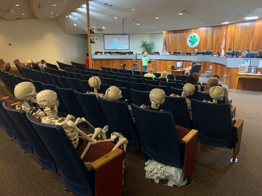 "Seven skeletons sit in seats at Tuesday's Santa Rosa County Commission meeting. Save Our Soundside President Dara Hartigan placed the skeletons there to represent what she said are ""life or death"" decisions being made by commissioners regarding subdivisions near possible toxic waste dumps."
