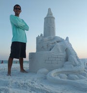 Sand sculptor Dan Anderson stands beside a dragon castle he created at the Crab Trap in Destin in 2019.