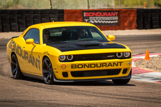Christian Bale drives a Dodge Challenger Hellcat at the Bondurant High Performance Driving School in Chandler, with Rob Knipe instructing from the passenger seat.