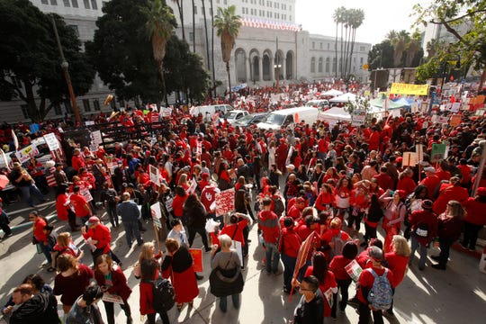 Los Angeles police officers guard the entrance to City Hall as teachers, parents and students picket outside City Hall in Los Angeles,  Jan. 18, 2019.