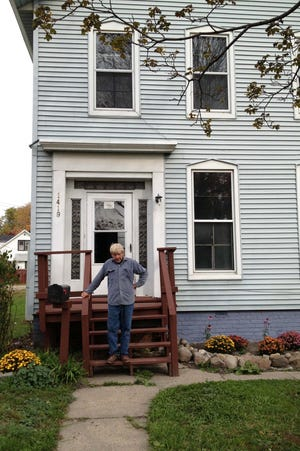 Henry Hudson stands on the front porch of 1419 Lapeer Ave. in Port Huron. The 69-year-old man said he hasn?t given up on the home despite the City Council voting to demolish it.  LIZ SHEPARD/TIMES HERALD.