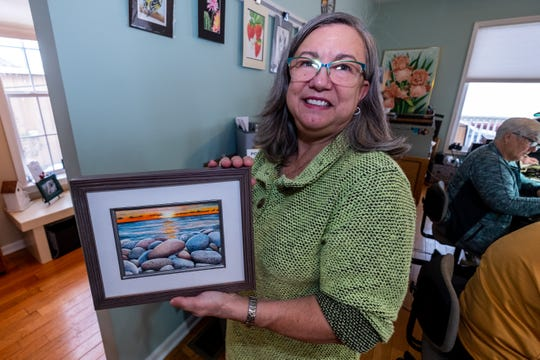 Valerie Hoste, a retiring computer skills teacher at SC4, holds a colored pencil painting she did Thursday, Nov. 14, 2019, in her Port Huron studio. Hoste is retiring from SC4 and plans to operate her studio full time.