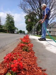 Henry Hudson waters flowers he planted along the 1400 block of Lapeer Avenue in Port Huron in 2014. He said it was a way to thank the community that helped him rehabilitate his home.