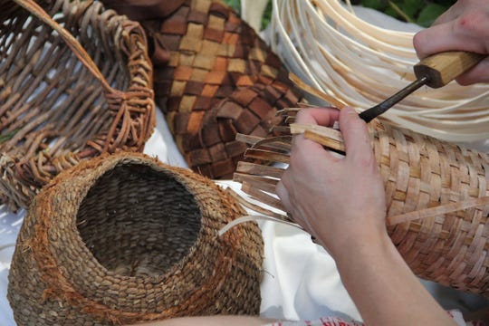 Katie Grove uses natural materials for weaving a basket.