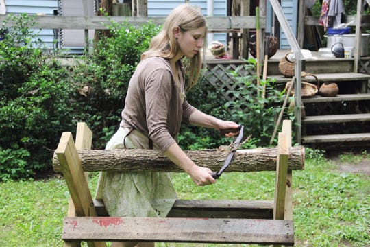 Katie Grove uses a drawknife to take the outer bark off a log for basket-weaving materials.