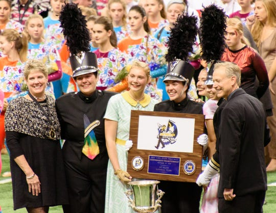 New York State Field Band Conference officials, on the left and right, present the first place plaque to, from second from left, drum major Phoebe Anderson, color guard captain Tori Smalley, drum major Anna Spendley, color guard captain Sophia Bodack and drum major Amanda Jacobs.