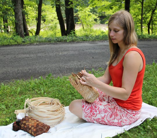 Katie Grove is shown weaving a basket with inner bark of a green ash tree.