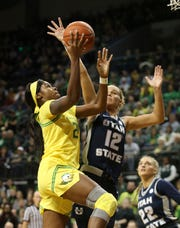 Oregon's Ruthy Hebard, left shoots next to Utah State's Hailey Bassett and Jocelyn Polansky, right