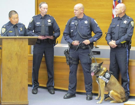 (from left) Salem police Lt. Dave Okada and Chief Jerry Moore give a medal of valor award to Officer Sean Cooper and his canine partner, Jack, while Deputy Chief Scott Hayes watches at Salem Police Department's annual awards  July 11, 2011.