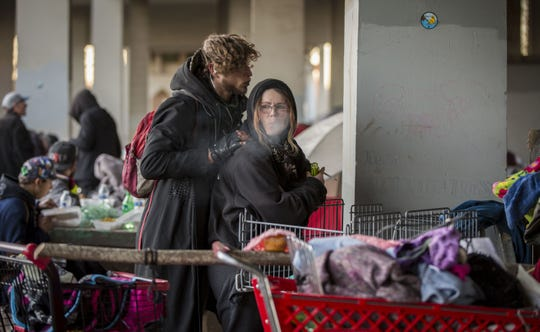 Members of the homeless camp located under the Marion Street Bridge near downtown Salem wait for food catered by BiBiM Bap House January 14, 2019.