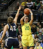 Oregon's Sabrina Ionescu, right, shoots over Utah State's Taylor Franson