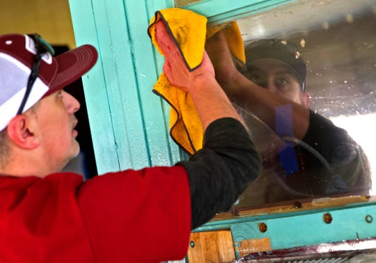 John McClairty, left, cleans a window on the exterior of the Boys and Girls Club north side building Thursday, Nov. 14, 2019.